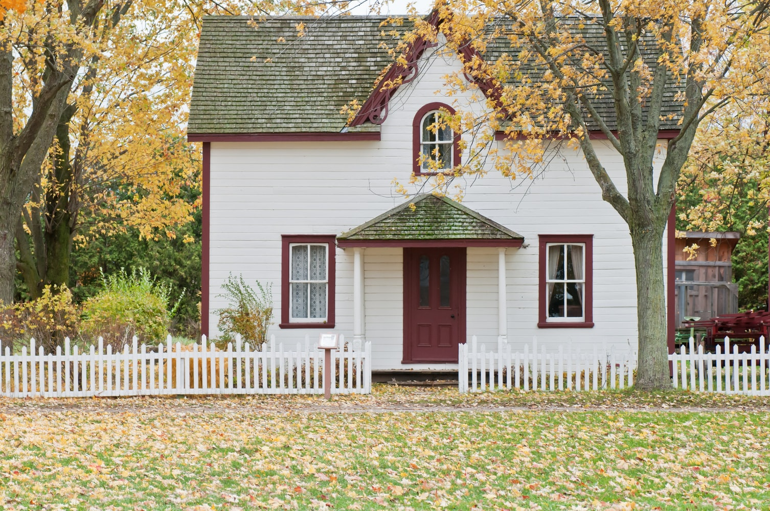Small White Home With Red Door and White Picket Fence