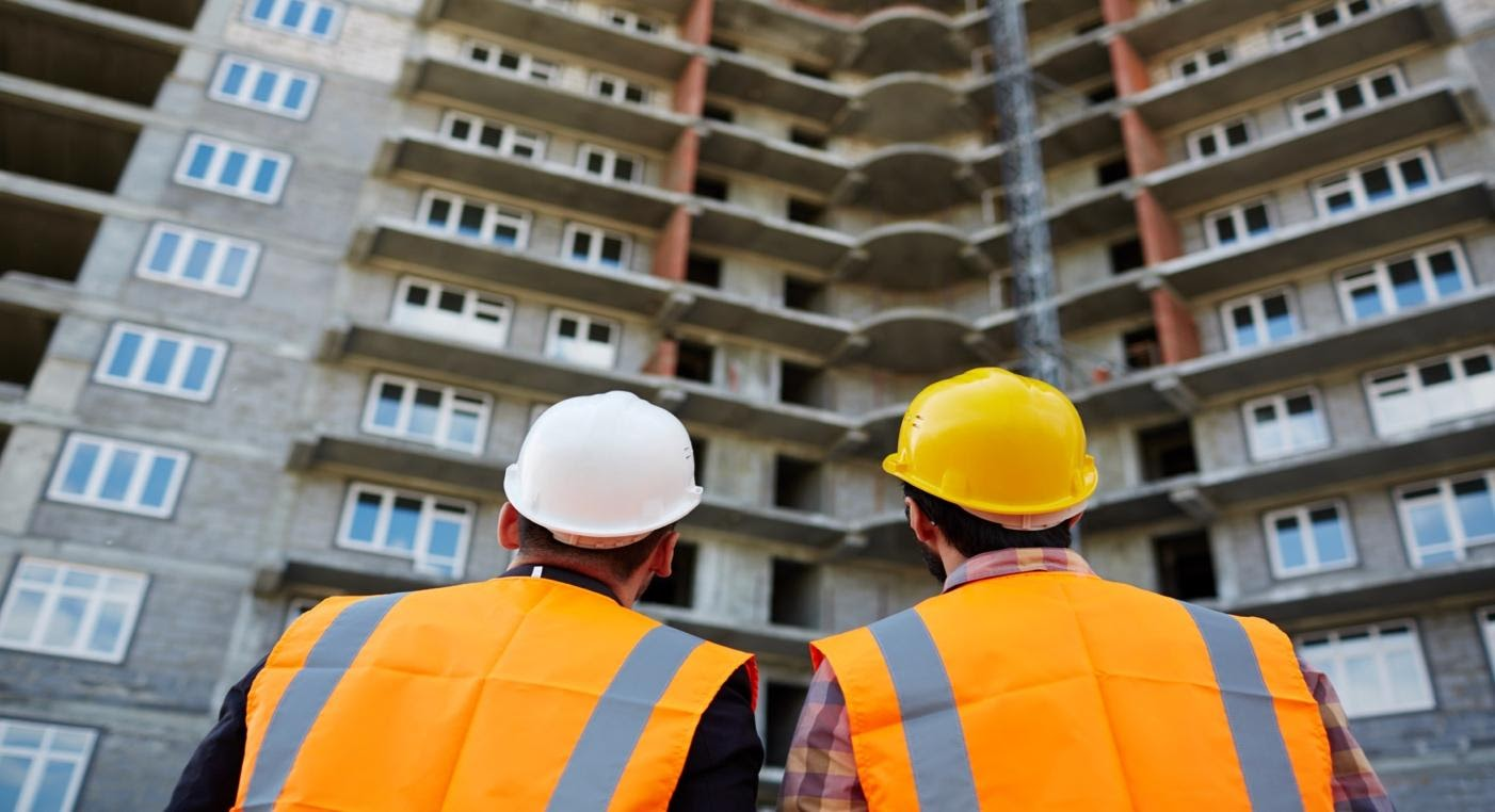 two construction workers looking up at an apartment building