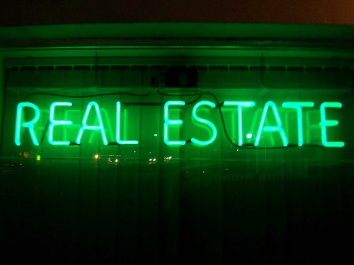 """a neon sign with the word """"real estate"""""""